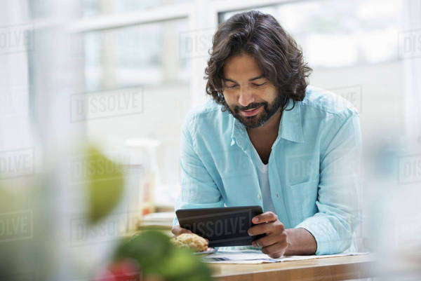 An office or apartment interior in New York City. A bearded man in a turquoise shirt using a digital tablet.  Royalty-free stock photo