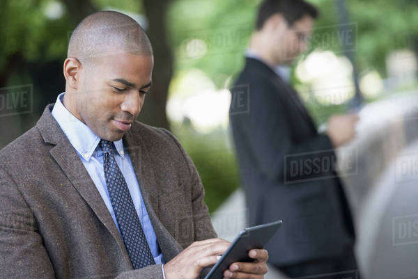 Business people in the city. Keeping in touch on the move. Two men in the park, one using a digital tablet, and one checking a smart phone.  Royalty-free stock photo