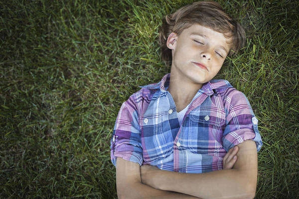 A boy with arms folded lying on the grass, eyes closed.  Royalty-free stock photo