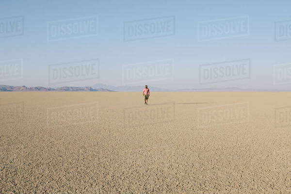 Man walking across a flat desert landscape Royalty-free stock photo