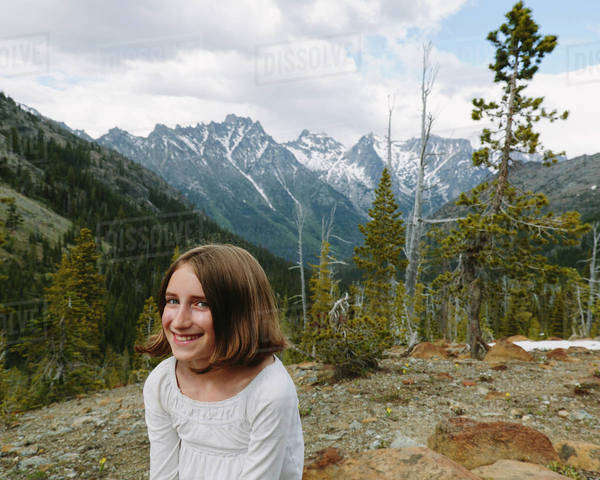 A young girl sitting at a lookout point, with a view over the mountains of Wenatchee national forest.  Royalty-free stock photo