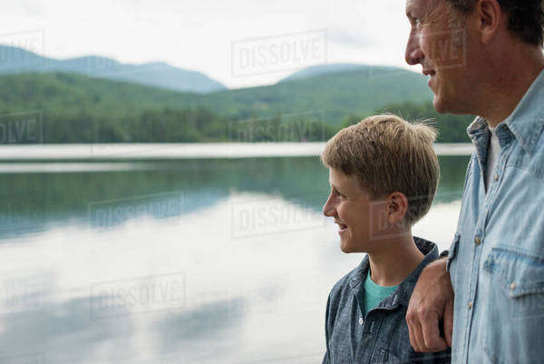 A family outdoors under the trees on a lake shore. Father and son.  Royalty-free stock photo