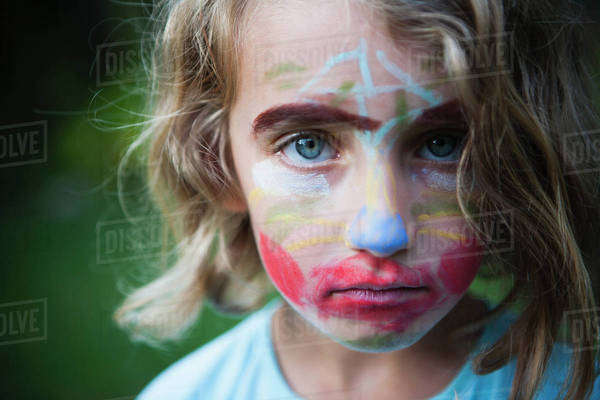 A young girl with a face decorated with face paints, wearing an unamused expression.  Royalty-free stock photo