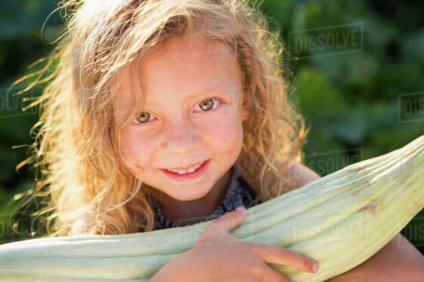 A young girl with long red curly hair outdoors in a garden holding a large fresh corn on the cob. Royalty-free stock photo