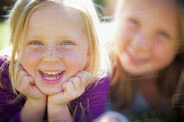 A portrait of two sisters smiling. Two young girls, with blue eyes and blonde hair. Lying on the grass. Close up. Royalty-free stock photo