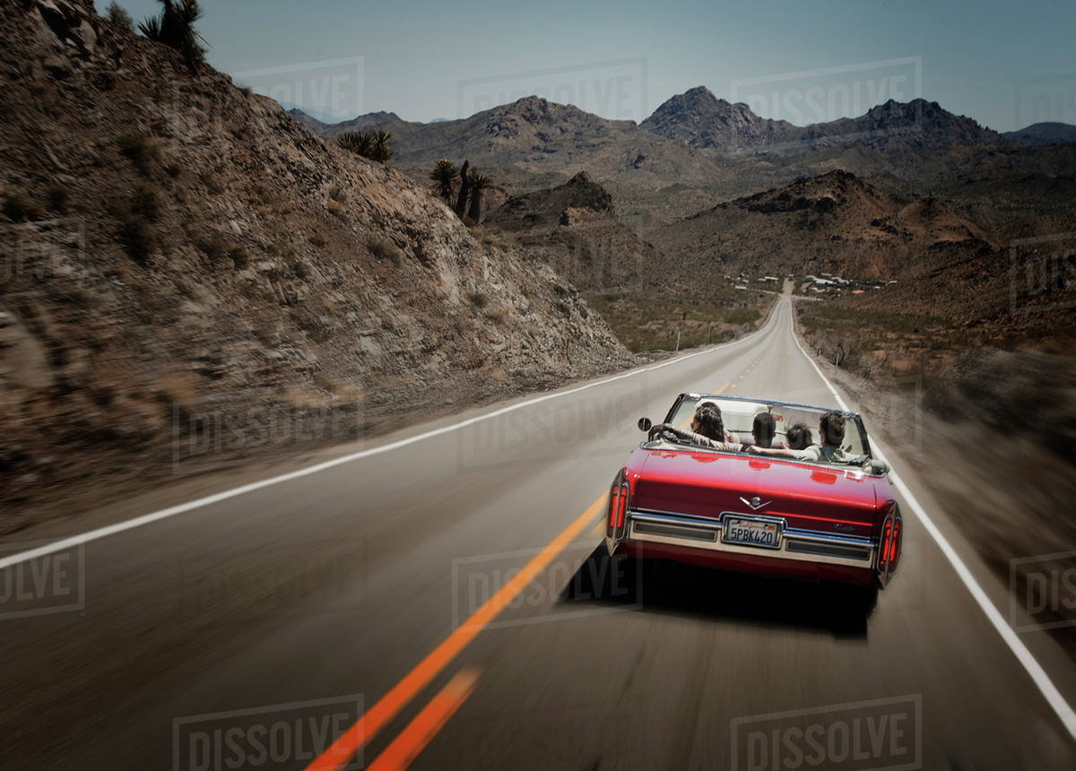 A Red Convertible Car With Five Young People On A Road Trip The Open Road Stock Photo Dissolve