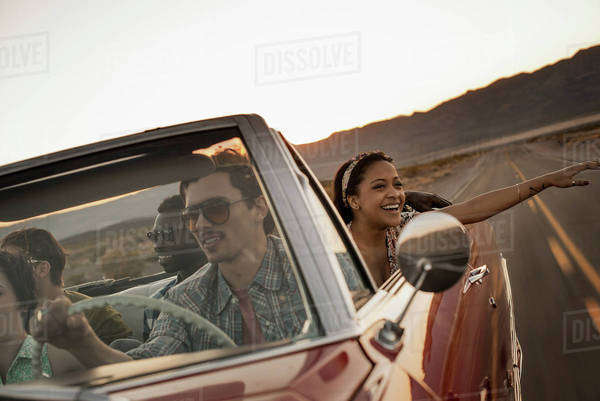 A group of friends in a red open top convertable classic car on a road trip.  Royalty-free stock photo