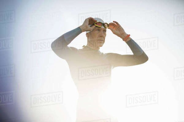 A swimmer in a wetsuit and swimming hat, adjusting his swimming goggles.  Royalty-free stock photo