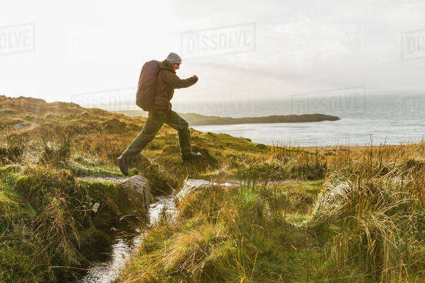 A man with a rucksack and winter clothing leaping across a small stream in an open exposed landscape.  Royalty-free stock photo