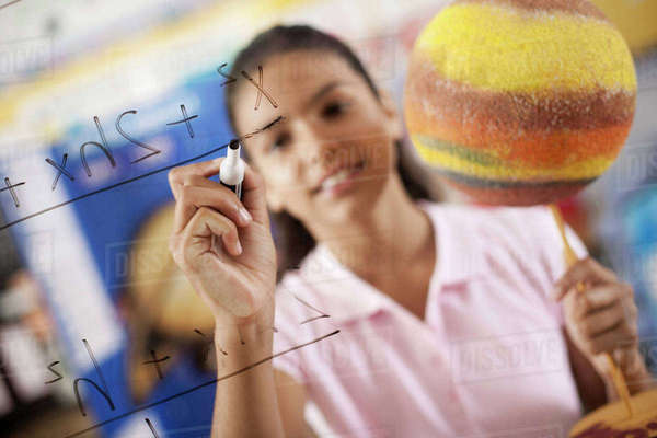 A girl writing with a pen on a board of equations and formulae in the classroom. Royalty-free stock photo