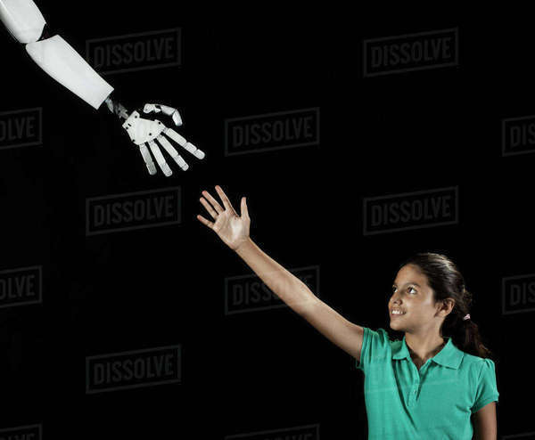A girl reaching up to touch a robotic hand.  Royalty-free stock photo