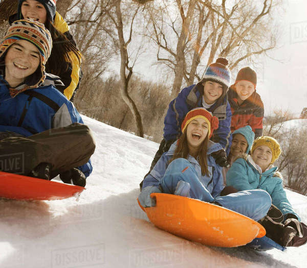 A group of children, boys and girls, riding on sledges on the snow.  Royalty-free stock photo