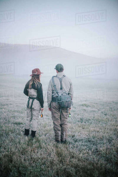 Two people walking across a meadow in early morning mist carrying fishing rods. Royalty-free stock photo