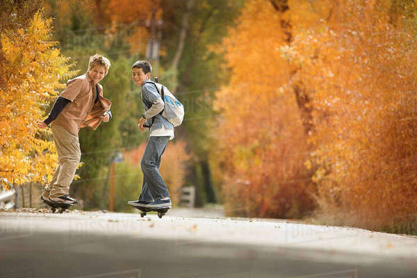 Two boys on skate boards on a roadway in woodland with vivid autumn foliage.  Royalty-free stock photo