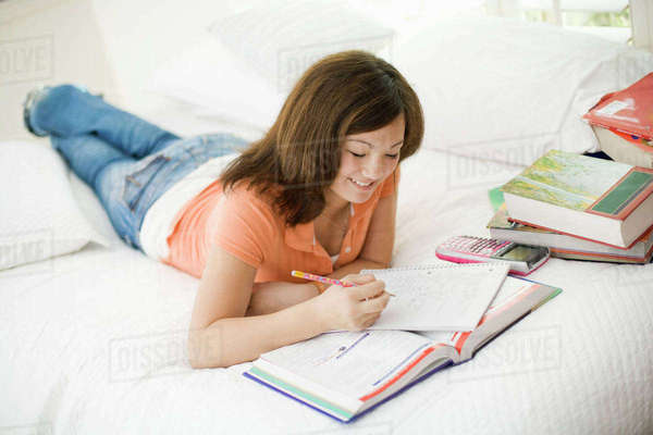 A girl lying on her bed holding a pencil and notebook.  Royalty-free stock photo