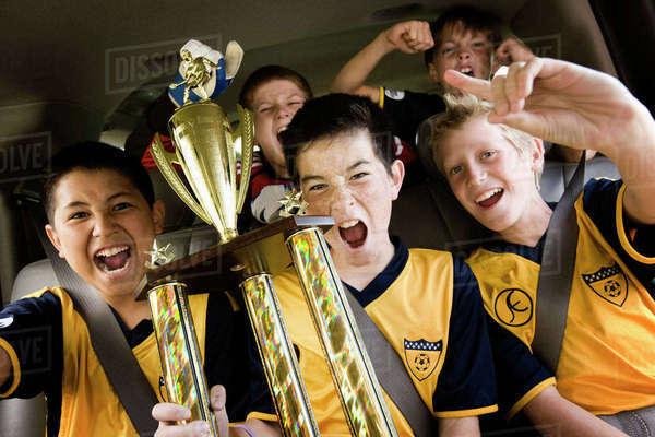 A group of boys in soccer team shirts holding a trophy and celebrating a win. In a team bus.  Royalty-free stock photo