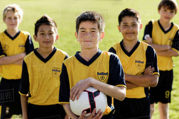 A group of boys in team football shirts, one holding a soccer ball.  Royalty-free stock photo