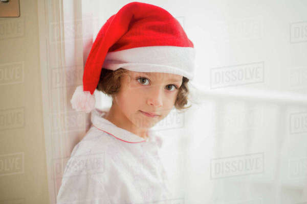 A young girl in a Santa hat on Christmas morning.  Royalty-free stock photo