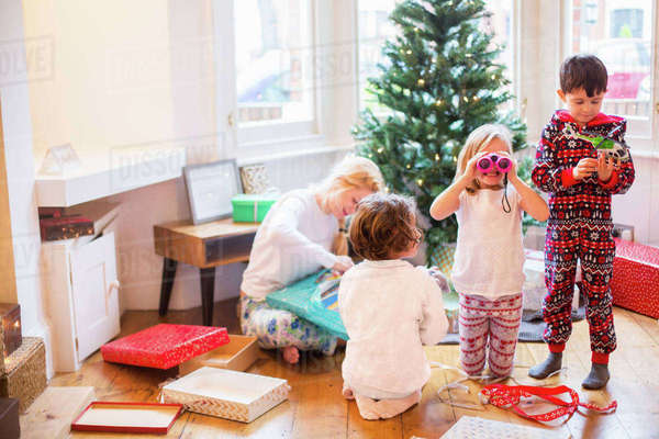 A mother and three children on Christmas morning opening presents.  Royalty-free stock photo