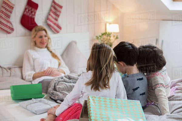 A woman in bed, with three children at the foot of the bed, carrying Christmas presents.  Royalty-free stock photo