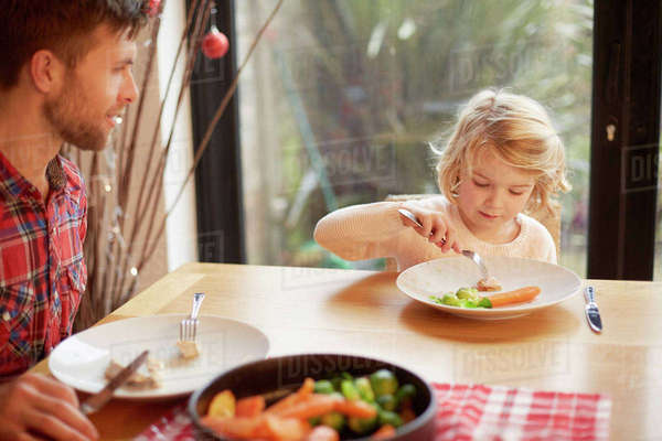 A child and a man sitting at a table eating a cooked meal.  Royalty-free stock photo