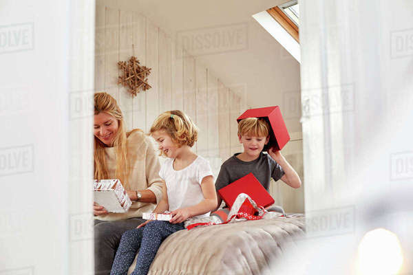 Christmas morning in a family home. A mother and two children sitting on a bed opening presents.  Royalty-free stock photo