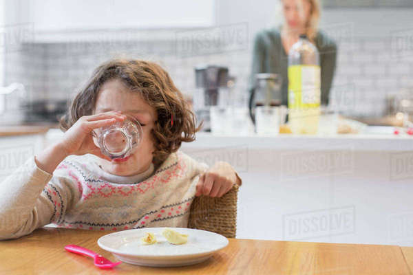 A child sitting at a table drinking from a glass, a woman standing behind her in a domestic kitchen.  Royalty-free stock photo