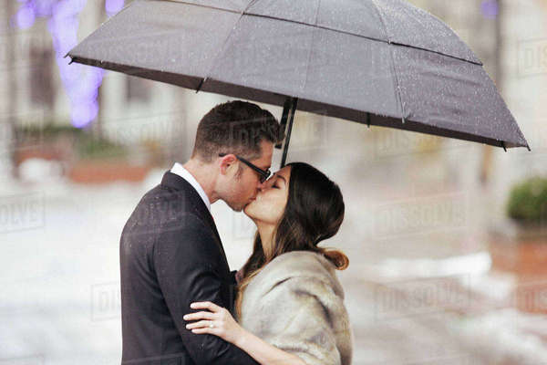 A couple in evening dress, a man and woman kissing under an umbrella.  Royalty-free stock photo
