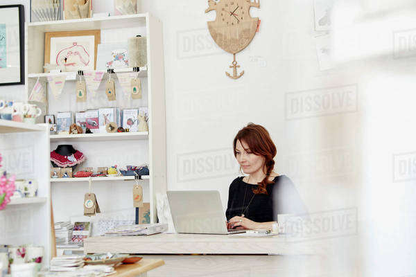 A woman sitting at a desk in a small gift shop, doing the paperwork, managing the business, using a laptop. Royalty-free stock photo