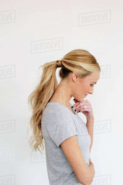 A young woman with blonde hair in a grey shirt, one hand on her chin. Royalty-free stock photo