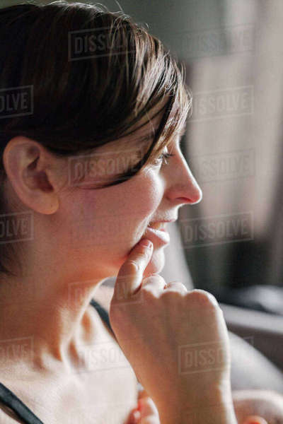 A woman in profile, with her hand to her chin.  Royalty-free stock photo