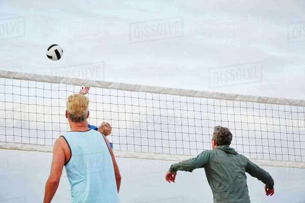 Mature men standing on a beach, playing beach volleyball.  Royalty-free stock photo