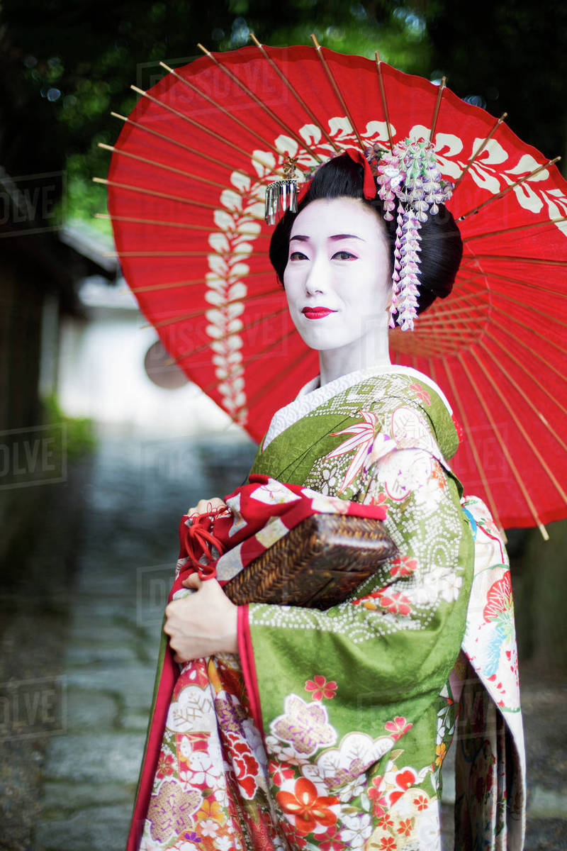 A Woman Dressed In The Traditional Geisha Style Wearing A