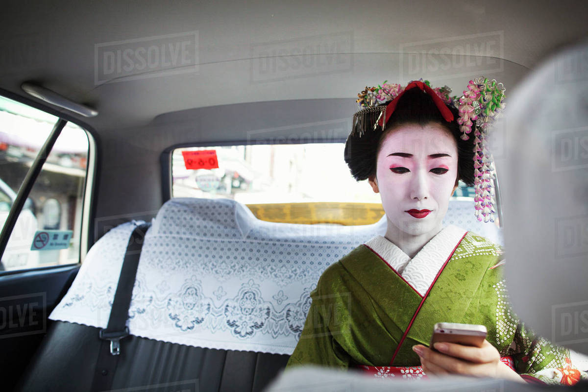 A woman dressed in the traditional geisha style, wearing a kimono with an elaborate hairstyle and floral hair clips, with white face makeup in a taxi, using a smart phone.  Royalty-free stock photo