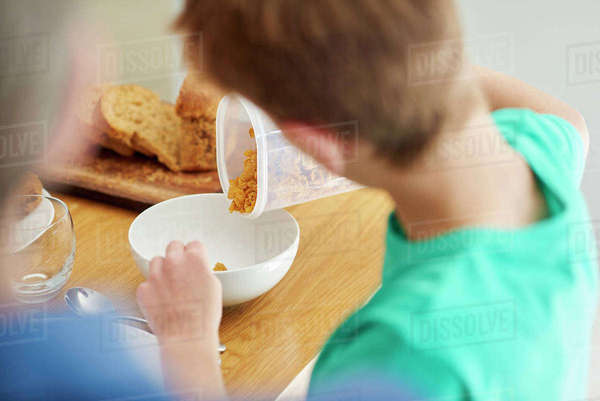 Breakfast. A boy pouring cereal into a bowl.  Royalty-free stock photo