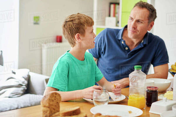 A father and son, man and boy sitting at the breakfast table.  Royalty-free stock photo