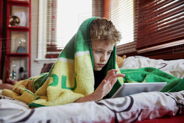 A boy with a towel over his head lying on his bed, using a digital tablet.  Royalty-free stock photo
