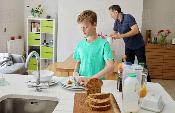 A family home. A man and a boy clearing away plates after breakfast.  Royalty-free stock photo