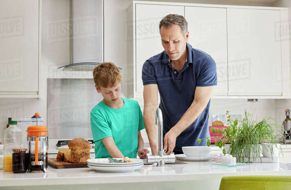 A family home. A man and a boy doing the clearing and washing up. Royalty-free stock photo