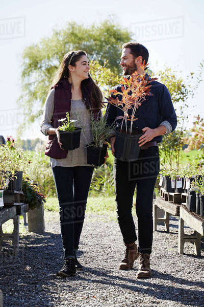 A young man and woman walking through displays at a garden centre, holding plants and looking at each other. Royalty-free stock photo