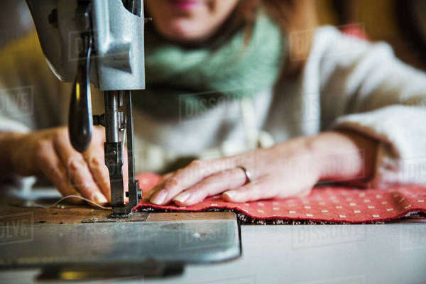 Upholstery workshop. A woman seated working with an industrial sewing machine, stitching fabric.  Royalty-free stock photo