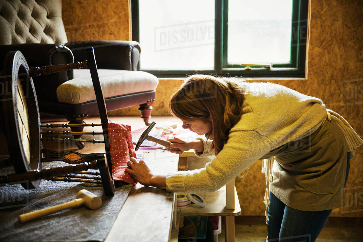 Upholstery Workshop A Woman Hammering Fabric And Padding To A Chair
