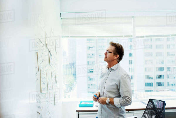 A man standing in an office looking at pieces of paper pinned on a whiteboard. Royalty-free stock photo