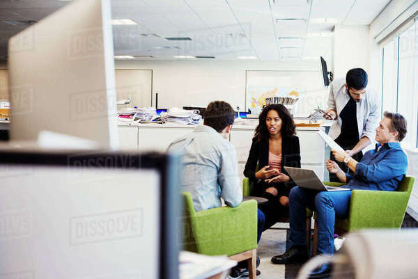 A woman and three men sitting and standing in an office talking to each other. Royalty-free stock photo