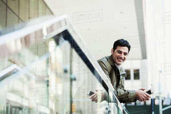 A young man leaning over a balcony rail holding a cellphone and smiling. Royalty-free stock photo