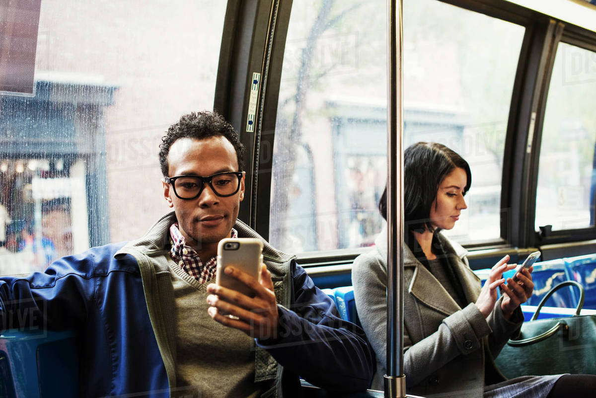 A young man and a young woman sitting on public transport looking at their cellphones. Royalty-free stock photo