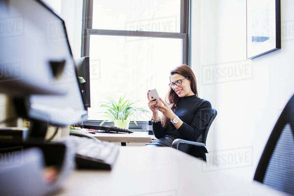 A young woman sitting at a desk in an office looking down at a cellphone. Royalty-free stock photo