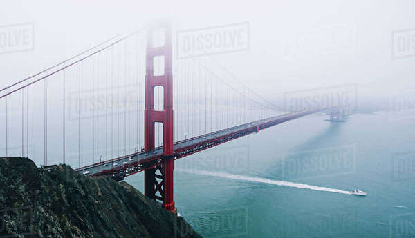 The Golden Gate bridge in the mist, with a boat sailing underneath. Royalty-free stock photo