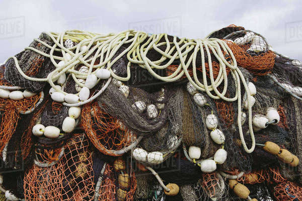 Close up of a pile of tangled up commercial fishing nets with floats attached. Royalty-free stock photo