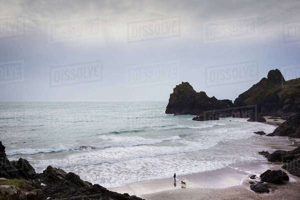 Cornish Coast, view of the sea from a rocky cliff, a person and dog standing on a sandy beach. Royalty-free stock photo